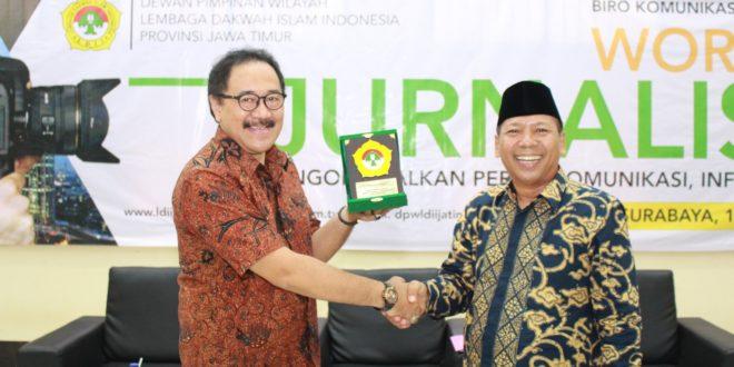 Komisaris Jawa Pos Grup Imawan Mashuri (kiri) mengangkat plakat yang diterima dari Ketua DPW LDII Jatim H.M. Amien Adhy (kanan)