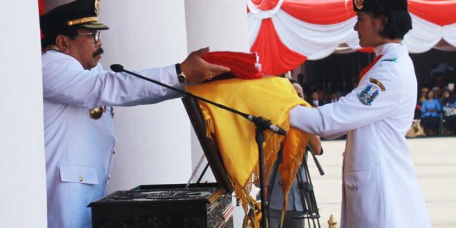 Gubernur Soekarwo menyerahkan bendera merah putih kepada paskibra di upacara peringatan HUT ke-71 Kemerdekaan RI di Gedung Negara Grahadi, Surabaya, Rabu (17/8).