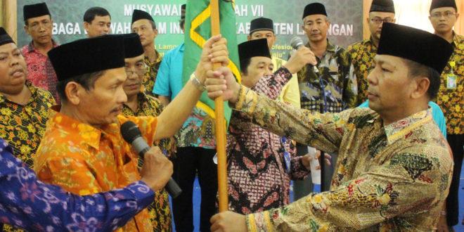 Ketua DPW LDII Provinsi Jawa Timur Drs. Ec. H. M. Amien Adhy (kanan) menyerahkan panji LDII kepada Ketua LDII Lamongan terpilih Ir. H. Bayu Widodo di Grand Mahkota Hotel Lamongan, Minggu (27/11).