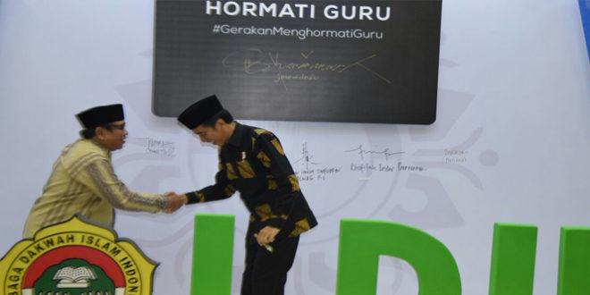 Presiden Joko Widodo berjabat tangan dengan Ketua Umum DPP LDII Abdullah Syam usai menandatangani wall of fame gerakan hormati guru di Balai Kartini Jakarta (9/11).